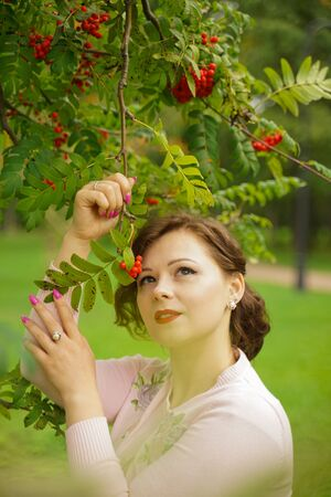 pretty woman picking chokeberry in the country