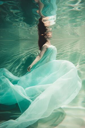 young woman swimming alone with fashion fabric underwater incognito
