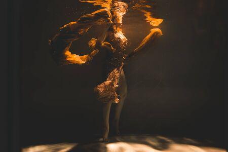 young woman swimming alone with fashion fabric underwater incognito Standard-Bild