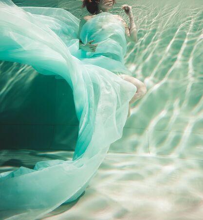 junge Frau schwimmt allein mit Modestoff unter Wasser inkognito Standard-Bild