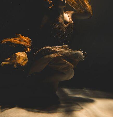 junge Frau schwimmt allein mit Modestoff unter Wasser inkognito