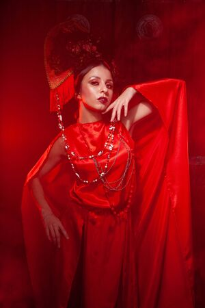strict stylish girl in a fashionable long red dress and a voluminous hat on the background of smoke in the Studio at night alone. Halloween concept. Archivio Fotografico