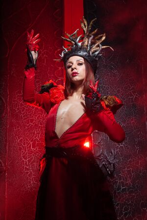 beautiful fashion witch woman with horns in the form of tree roots in a long luxurious dress on the background of a huge gate with red smoke. Halloween concept