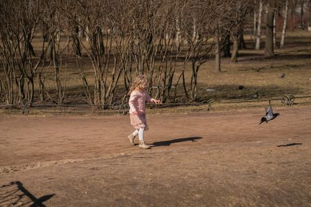 Pretty happy girl in pink jacket, cute skirt and warm pantyhose runs and scares the birds on sunny day in the city park alone Foto de archivo