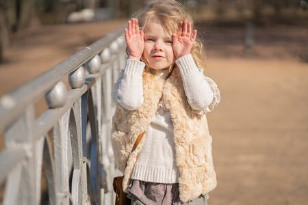 girl closing face with her hands and happy plays outdoor