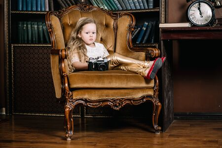 horizontal photo of happy beautiful little girl sitting in big golden cozy chair with photocamera