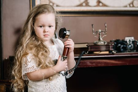 Little brooding child girl talking on a retro telephone in the room alone with sad emotions Imagens