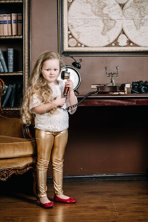 Little brooding child girl talking on a retro telephone in the room alone with sad emotions