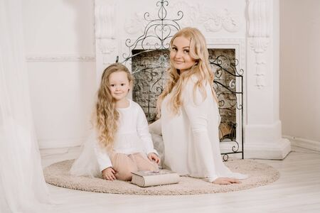 Story Time with Mother and Daughter in Front of Fireplace. Pretty family with book. Mom and child sitting close and happy hugs.