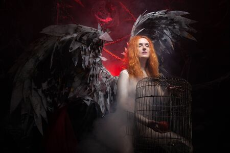 an evil tempting woman with large demon wings holds an Apple in a large cage and beckons to sin. Halloween photo plus size girl with red hair on a huge Gothic throne.