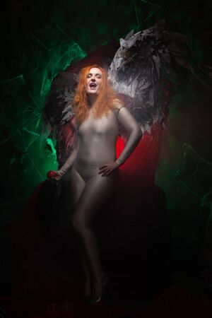 Mysterious plus size red hair girl in skincolor beige outfit with black and white big demon wings on gothic cemetery. Witch or dark angel style. Woman tempts by apple in the middle of the night