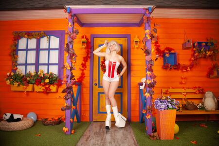 futuristic woman in white red corset and in huge white platform freak boots ready for halloween party and posing near her orange house