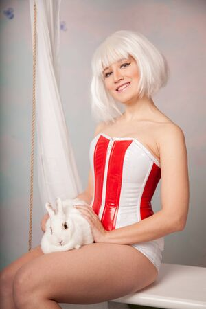pretty futuristic girl with short bob haircut in latex corset with her pet bunny together in the studio Stock Photo