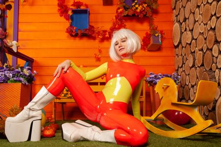 hot pretty blonde woman in bright colorful latex rubber catsuit ready for halloween autumn party and posing near her orange house