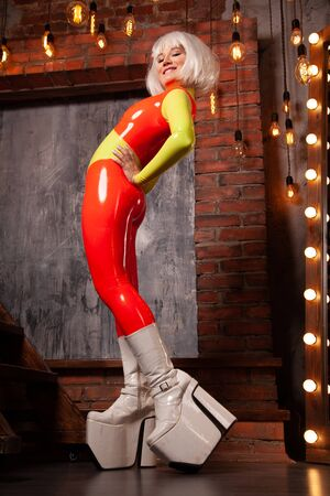 hot high fashion female in bright orange with lime green rubber outfit. beautiful futuristic woman in tight latex catsuit posing alone at home.