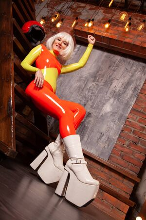 hot high fashion female in bright orange with lime green rubber outfit. beautiful futuristic woman in tight latex catsuit posing alone at home. Stock Photo - 138256156