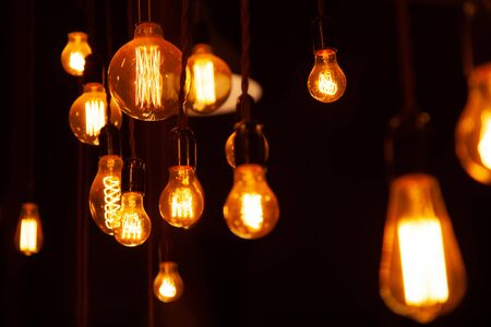 différentes ampoules rétro classiques accrochées sur fond de mur de briques la nuit
