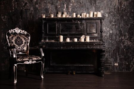 old black vintage piano with white candles and retro chair. nobody.