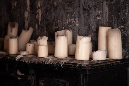 many old white candles on black table with nobody.