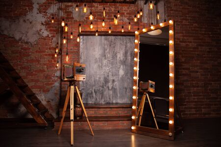 a very old rarity photo camera stands on a tripod near a huge mirror with lights in the Studio with brick background. nobody. copy space Reklamní fotografie