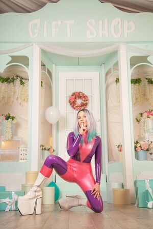 pretty cute adult girl in purple latex rubber costume posing near gift shop with presents and air balloons. woman in tight outfit posing alone. full length portrait.