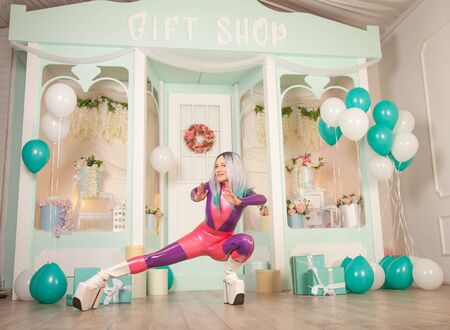 pretty cute adult girl in purple latex rubber costume posing near gift shop with presents and air balloons. fetish woman in tight outfit posing alone. full length portrait. 版權商用圖片