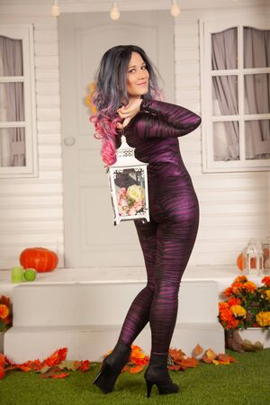 pretty halloween woman in tight tiger jumpsuit ready to celebrate and waiting for friends for a party outdoor