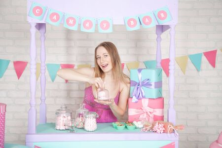happy woman with sweets and cakes in her purple candy bar Zdjęcie Seryjne