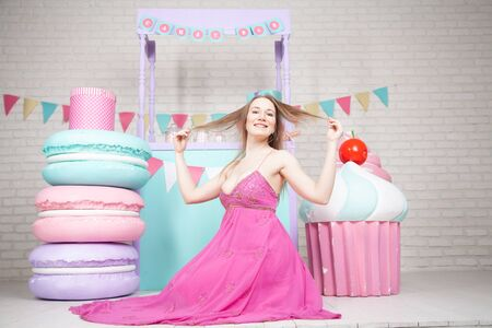 cute happy adult girl posing in fashionable dress among huge fabulous sweets and cakes Zdjęcie Seryjne