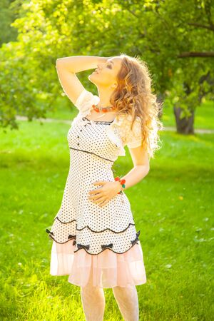 Young woman in white cute polka dot dress walking in an apple garden on a lovely sunny summer day