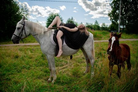 Beautiful caucasian young girl walking with a horse and enjoys summertime in countryside.