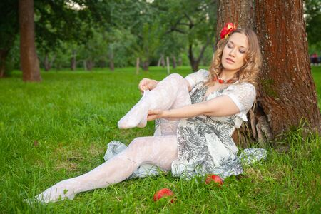 Young fashionable girl in white summer dress and lace stockings sitting on summer grass in the evening