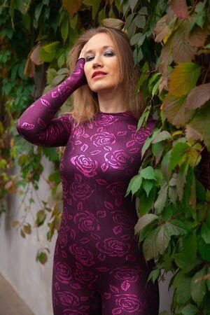 pretty girl in tiger costume pose in Wild grape leaves Zdjęcie Seryjne