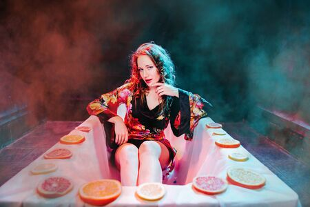 Young woman relaxing in Spa bath with slices of oranges. Welness concept.