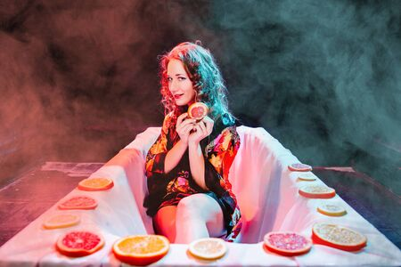 Young woman relaxing in Spa bath with slices of oranges. Wellness concept. 版權商用圖片