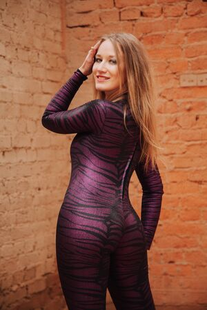 young plus size adult girl in Black Spandex Catsuit with tiger pattern walking in the old city Stock Photo
