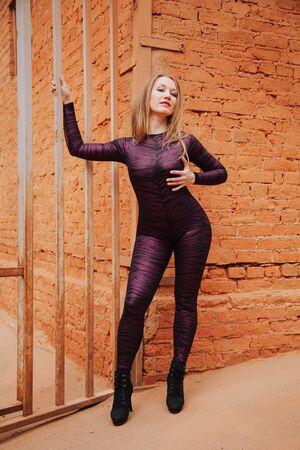 Jeune fille adulte taille plus en catsuit en spandex noir avec motif tigre marchant dans la vieille ville