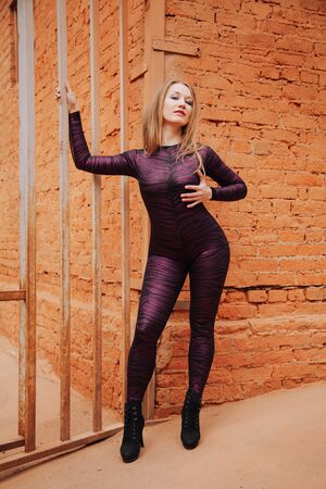 young plus size adult girl in Black Spandex Catsuit with tiger pattern walking in the old city