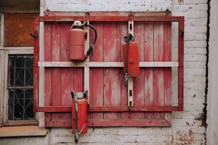 3 Fire extinguishers on the red old wall