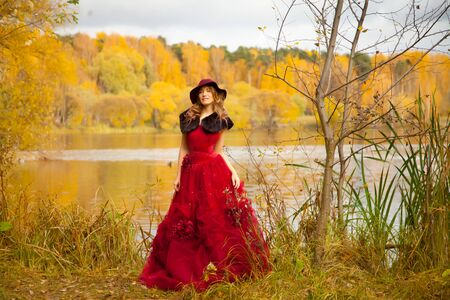Young woman in red fashion long dress with fur and hat walking in the autumn garden background alone