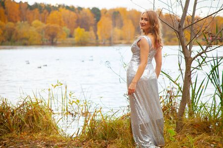 beautiful plus size girl in silver long dress posing near the pond in the autumn city Park alone
