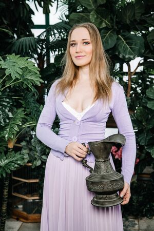 beautiful girl in purple dress stands with old vase in the greenhouse among the plants and enjoys the clean air and harmony of communication with nature Zdjęcie Seryjne - 136809047