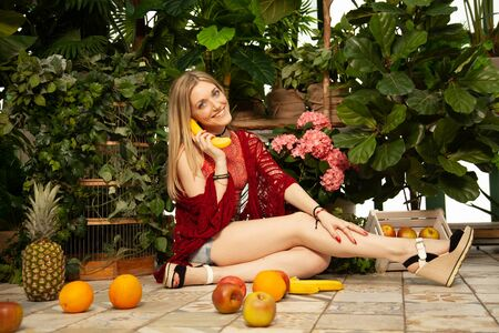 beautiful vegan woman in a red sweater and denim shorts sits on the floor next to scattered different fruits and rests from the city noise in the greenhouse and breathes fresh air