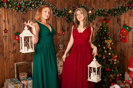 two elegant women in red and green long evening dress posing near christmas tree indoors Zdjęcie Seryjne - 136600400