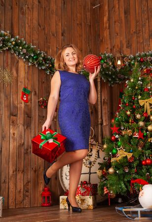 Christmas happy plus size girl in blue dress on xmas background room with wooden walls.