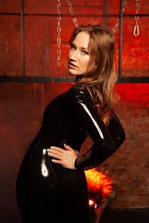 latex rubber woman in fashion black costume posing alone in the red light