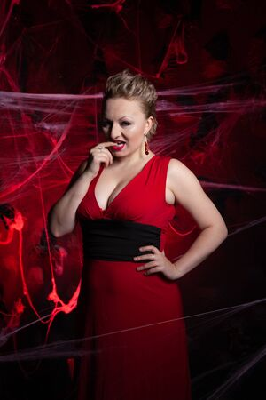 Woman in evening classic dress posing on black Halloween background with spider web Zdjęcie Seryjne - 136600433