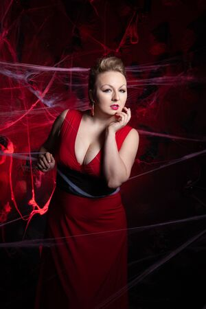 Woman in evening classic dress posing on black Halloween background with spider web Zdjęcie Seryjne - 136600435