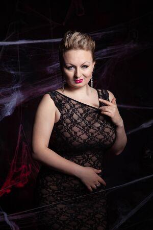 Woman in evening classic dress posing on black Halloween background with spider web Zdjęcie Seryjne - 136600440