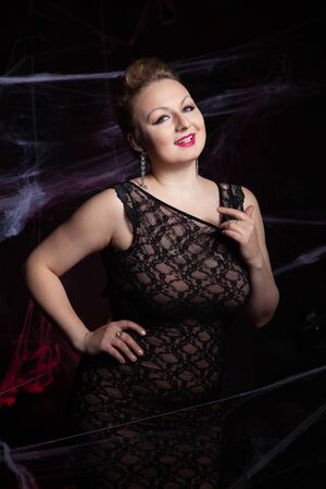 Woman in evening classic dress posing on black Halloween background with spider web Zdjęcie Seryjne - 136809833